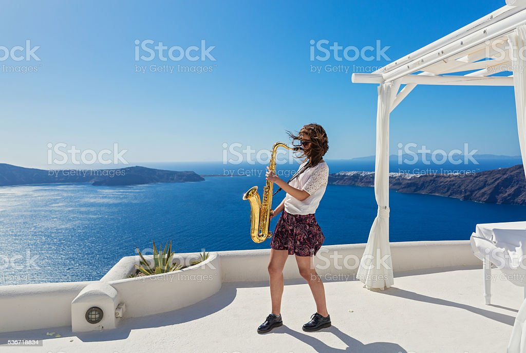 Girl,  saxophone and  sea stock photo