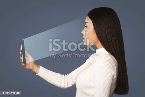 851960142 istock photo Girl scanning face with facial recognition system on smartphone 1198228346