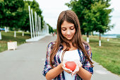 istock Girl schoolgirl 13-16 years old stands in summer city hands toy heart. Free space text. Happy smiles. Concept donation, blood life, gift, Valentine's Day. Help and donation of organs in hospital. 1136049113