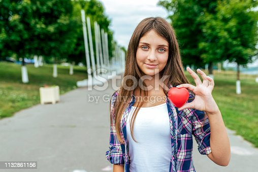 Girl schoolgirl teenager 11-14 years. In his hand a toy heart. Happy smiling in a city summer park. The concept of helping blood to organ donation, life saving, give a new life. Free space for text.
