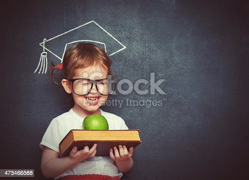 istock girl schoolgirl with books and apple in a school board 473466588