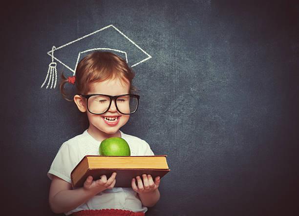 Niña en edad escolar Chica con libros y manzana en una escuela de planchar - foto de stock