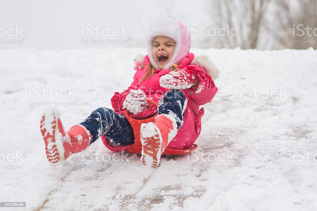 girl screaming and shrieking ice slides down hill stock photo
