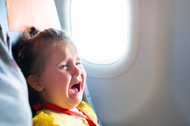 Girl Screaming On Airplane Little Girl Sitting Next To Mother Screaming On Airplane crying stock pictures, royalty-free photos & images