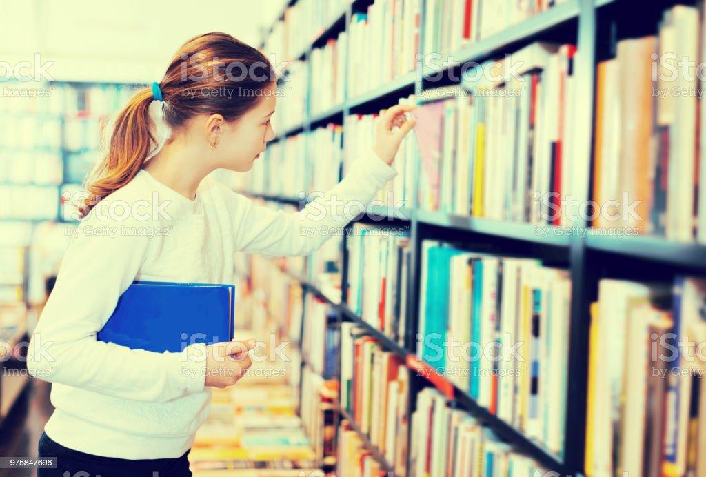 Mädchen auf der Suche nach Lehrbüchern über Bücherregale - Lizenzfrei Aussuchen Stock-Foto