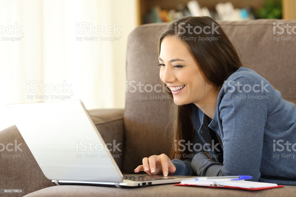 Girl searching online content in a laptop at home stock photo