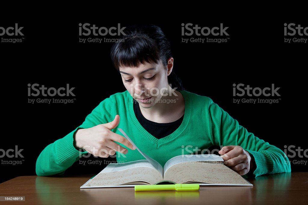 Girl searching through the dictionary's pages royalty-free stock photo