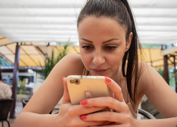 Girl seating in restaurant chating, and looking in phone stock photo