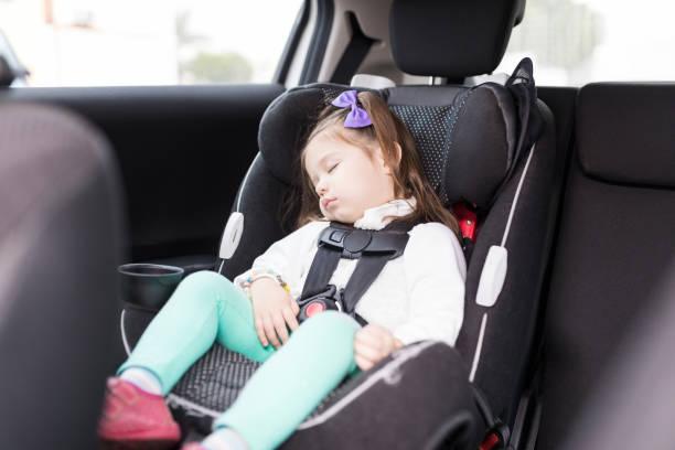 jeune fille sécurisée avec ceintures de sécurité, au repos dans la voiture - child car sleep photos et images de collection