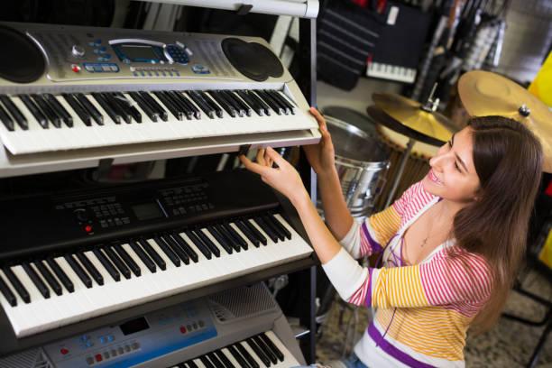 mädchen sie kontrolle der tastatur - klavier verkaufen stock-fotos und bilder