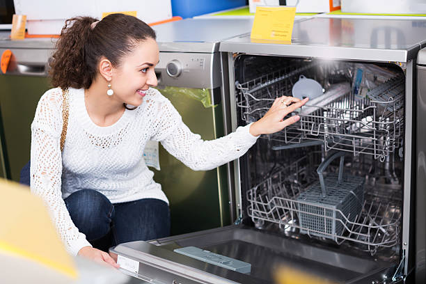 girl selecting modern dishwasher - commercial dishwasher stock photos and pictures