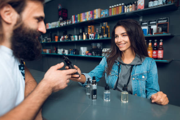 Girl seller shows the choice of electronic cigarettes in vapeshop. stock photo