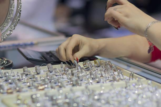 mädchen - verkäufer zeigt den schmuck an der theke. vertrieb - diamanten kaufen stock-fotos und bilder