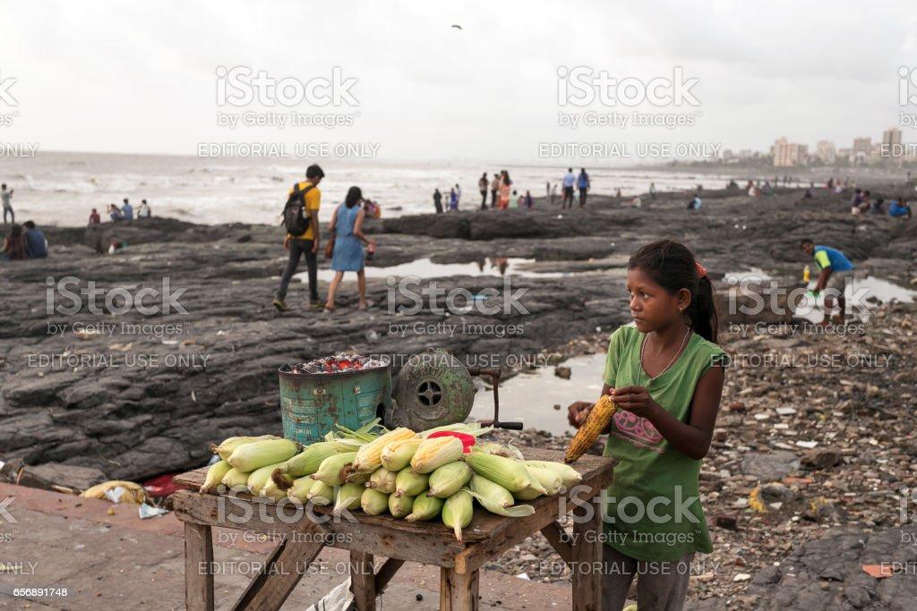 Girl selling corn cobs on Mumbai beachfront, Mumbai, India stock photo