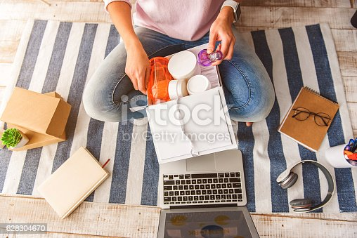 Top view close-up of young woman hands taking perfume from cosmetology gift box. She is sitting on floor near laptop at home