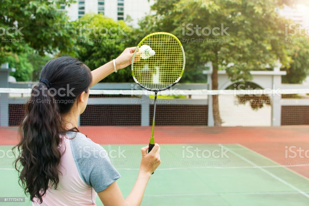 Girl serving on a badminton match outdoors stock photo