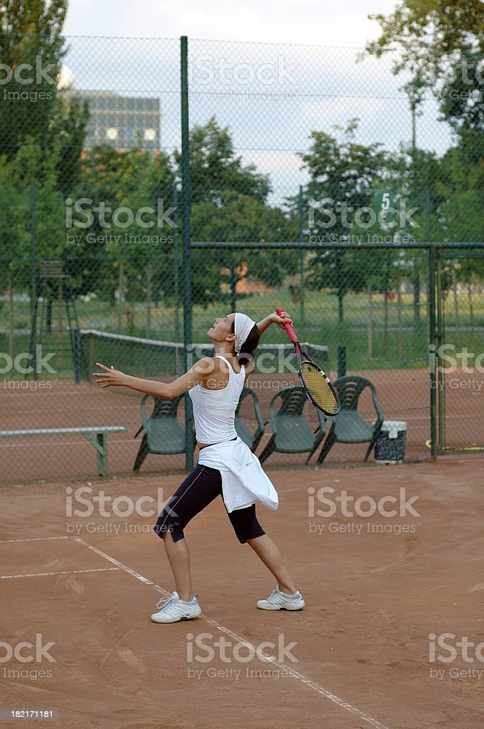 Girl serving on a tennis court, footfault royalty-free stock photo