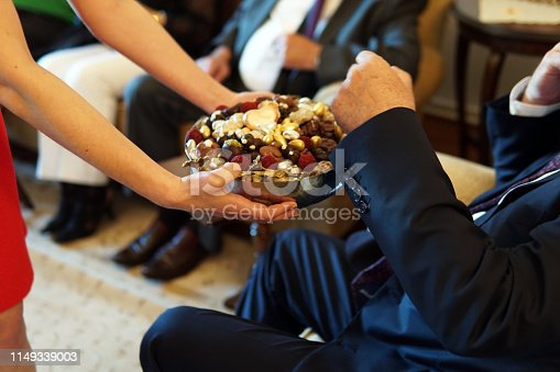istock girl serving turkish delight to old people, a traditional ceremony for Ramadan feast known as Eid Al Adha 1149339003