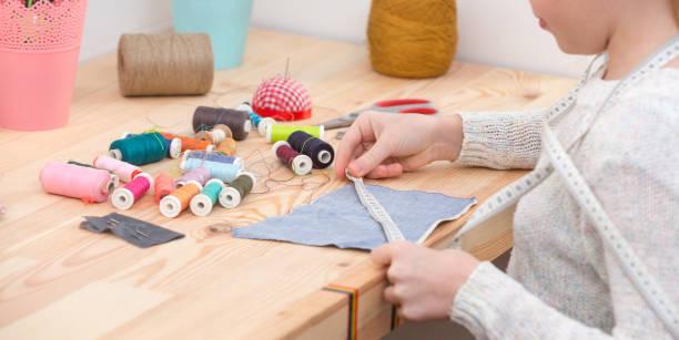 girl sews doll clothes – zdjęcie