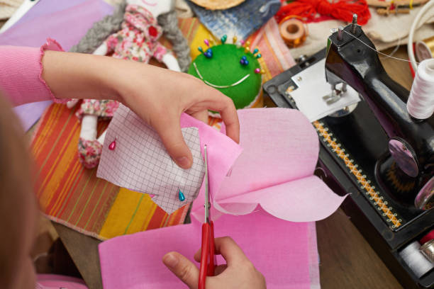 girl sews doll clothes, top view, sewing accessories top view, seamstress workplace, many object for needlework, handmade and handicraft - nähpuppen stock-fotos und bilder