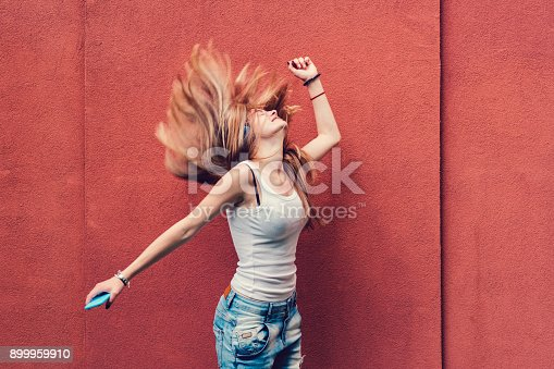 istock Girl shaking head to music 899959910
