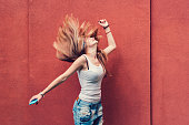 Teenage girl dancing to the music against red wall