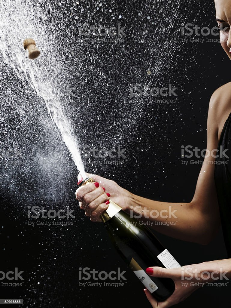 Girl shaking up bottle of champagne stock photo
