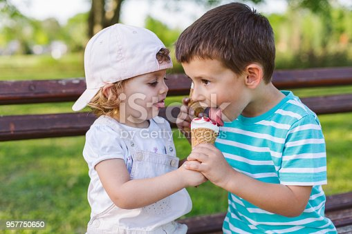 958492394 istock photo girl share her ice cream with brother 957750650