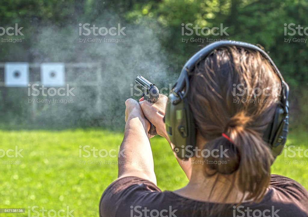 Girl shooting with a gun stock photo