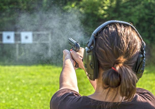 girl shooting with a gun - tarcza broń zdjęcia i obrazy z banku zdjęć