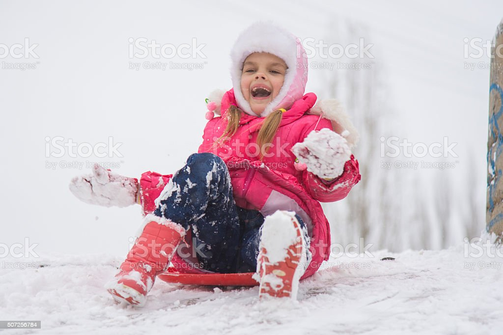 Girl shouting and rejoicing rolling ice slides stock photo