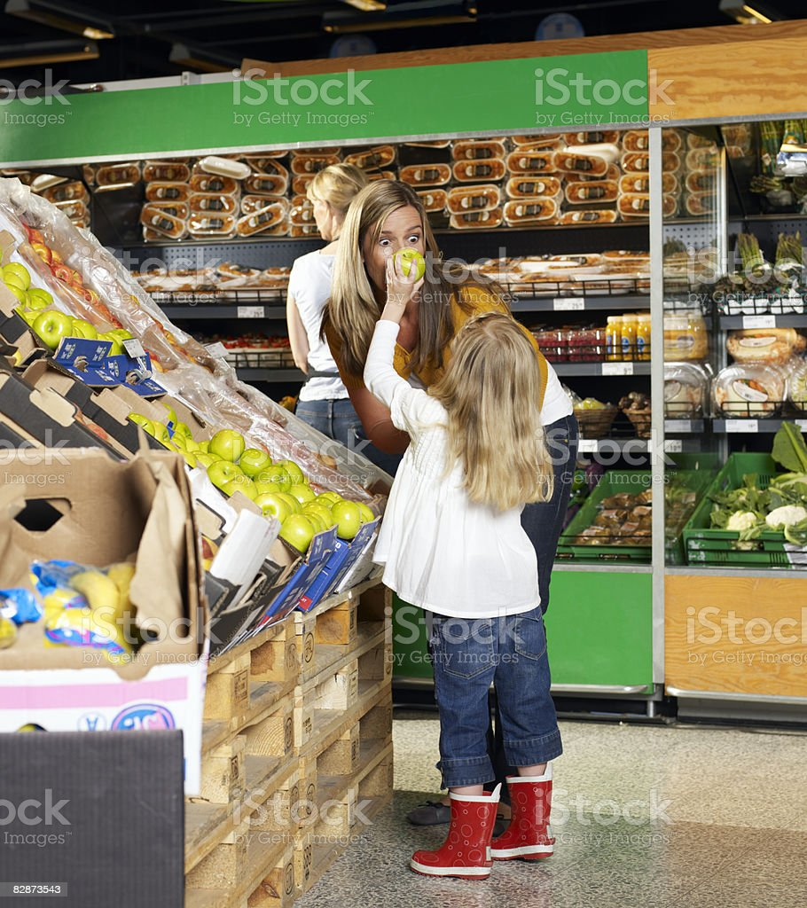 Girl (4-5) showing apple to mother in supermarket zbiór zdjęć royalty-free