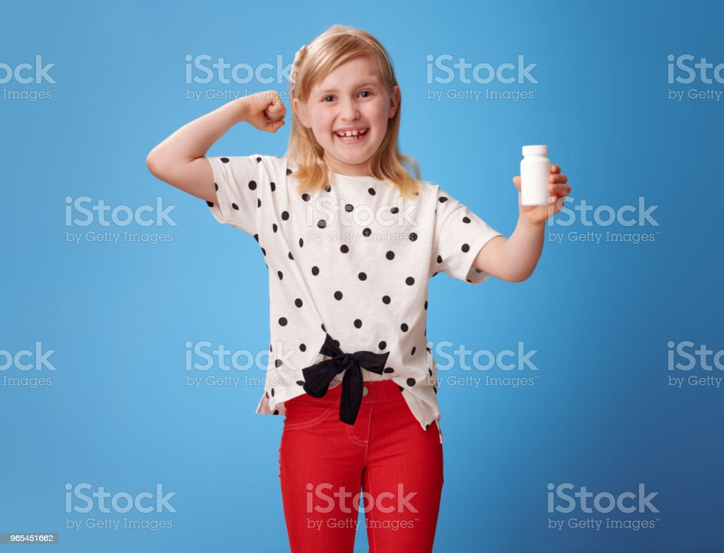 girl showing bottles of vitamins and biceps gesture on blue zbiór zdjęć royalty-free