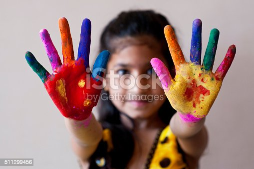 Little girl showing her painted hands with powder paint during Holi festival.