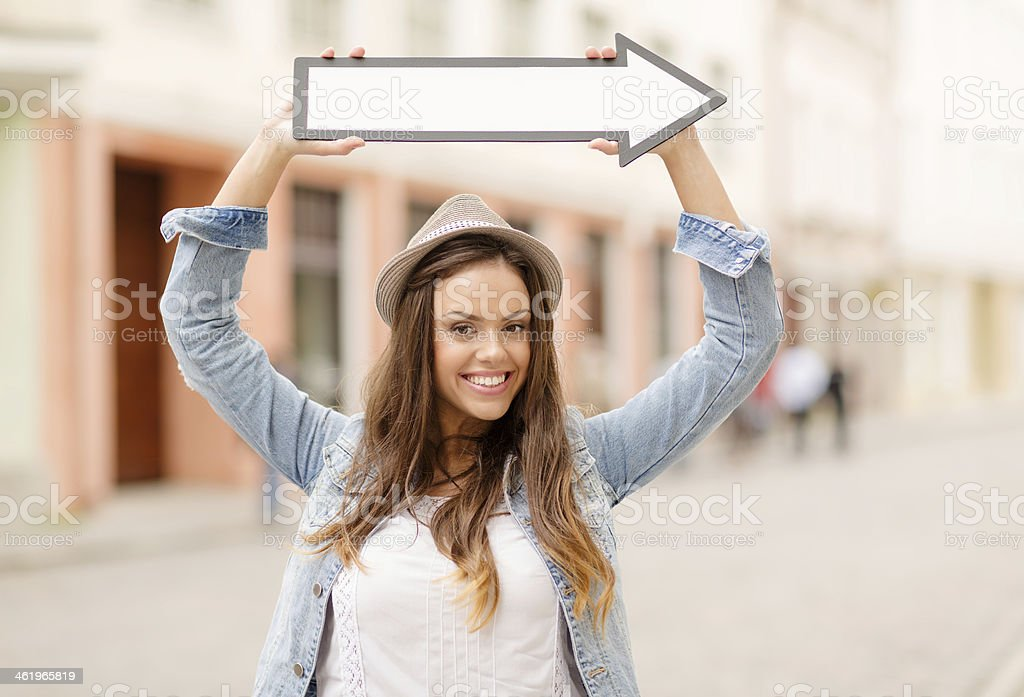 girl showing direction with arrow in the city stock photo