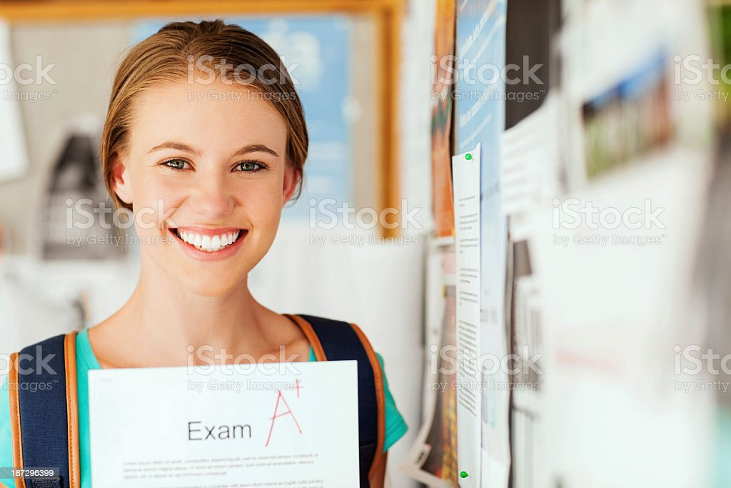 Girl Showing Exam Report With A+ Grade In College royalty-free stock photo