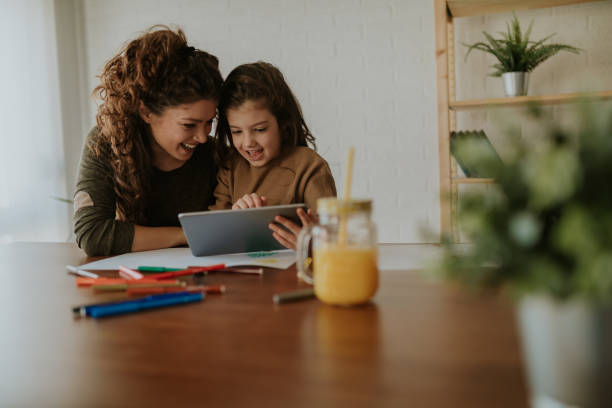 Girl showing her mom new games on her tablet. Sitting at table, taking a break from doing homework. Girl showing her mom new games on her tablet. Sitting at table, taking a break from doing homework. homework stock pictures, royalty-free photos & images