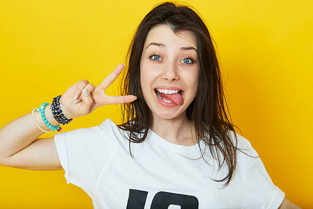 Girl showing her tongue and peace gesture stock photo