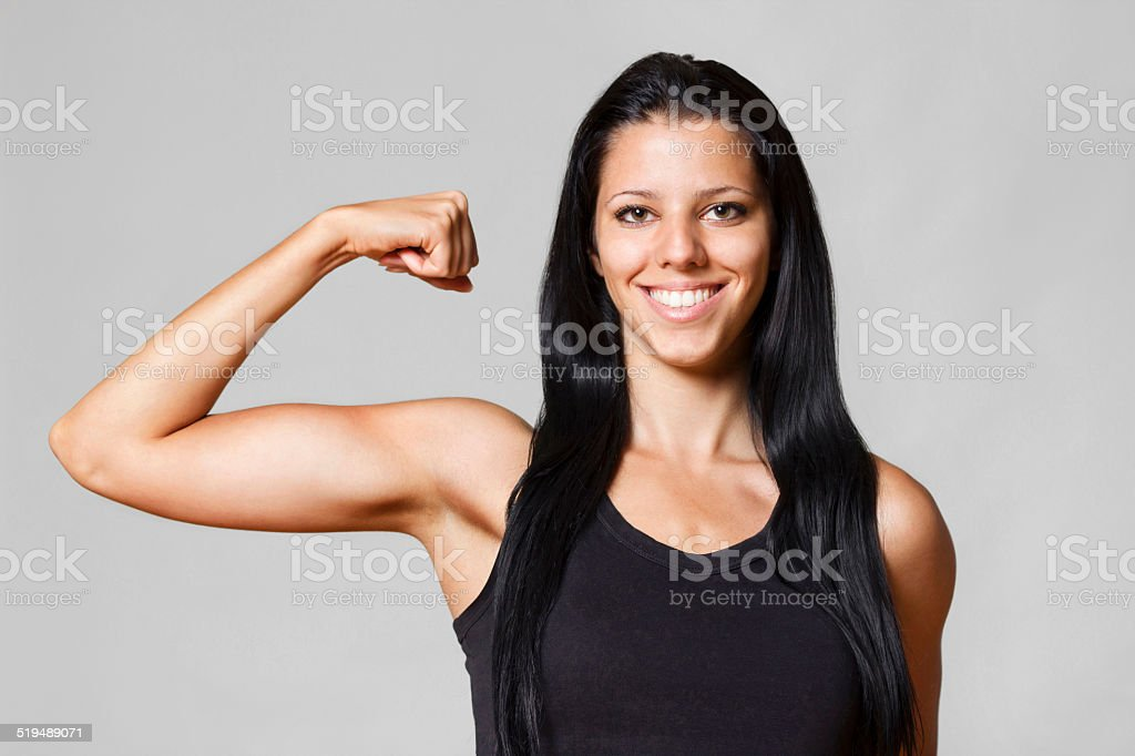 Girl showing off biceps stock photo