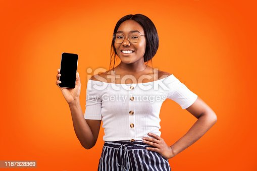 1159261513 istock photo Girl Showing Smartphone Blank Screen Smiling Standing Over Orange Background 1187328369