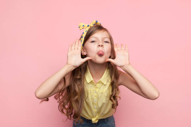 Girl showing tongue at camera Little charming model looking at camera and showing tongue on pink background. mischief stock pictures, royalty-free photos & images