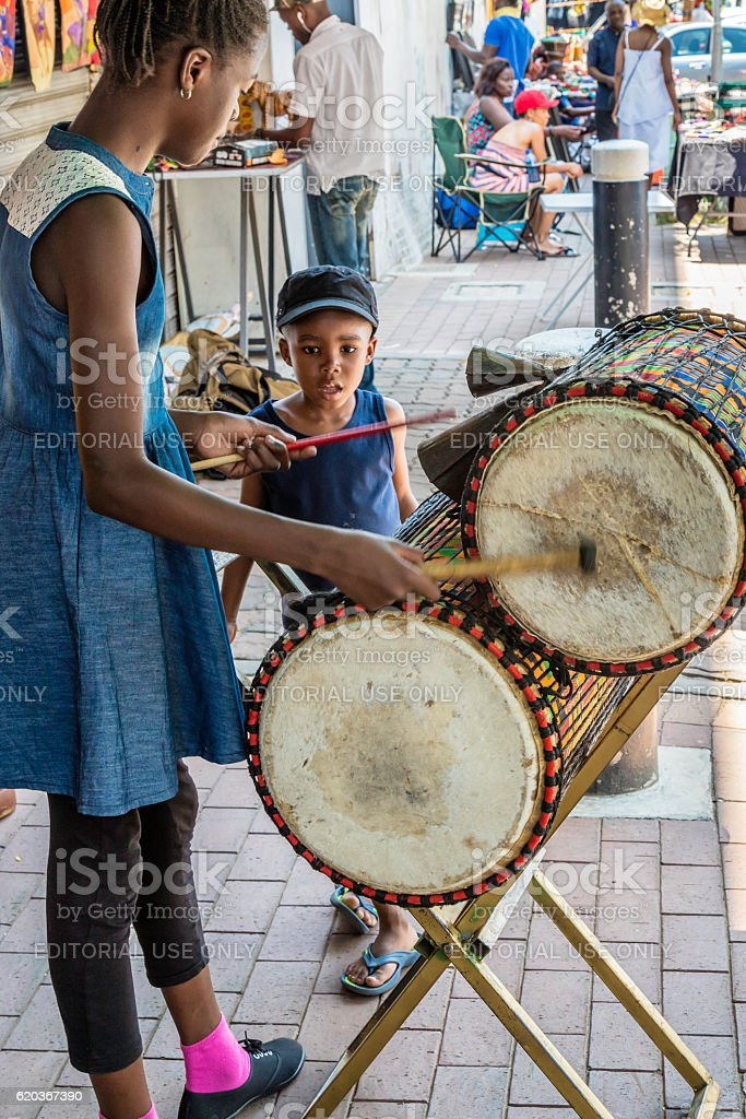 Girl showing younger brother how to play drums foto de stock royalty-free
