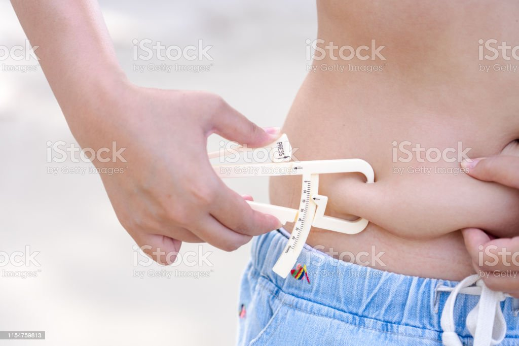 Girl Shows Holding And Pushing The Skin Of The Belly Cellulite With Personal Body Fat Tester Stock Photo Download Image Now Istock