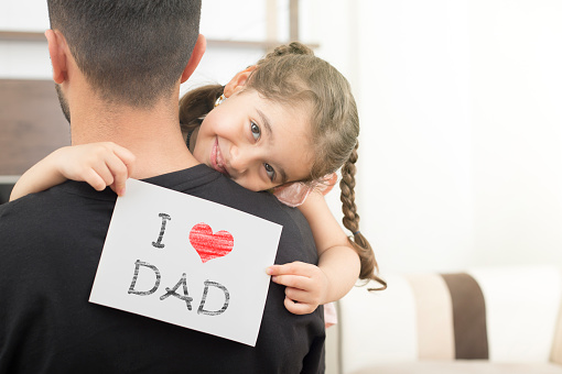 istock girl shows love dad card on her dad's shoulder 1152924900