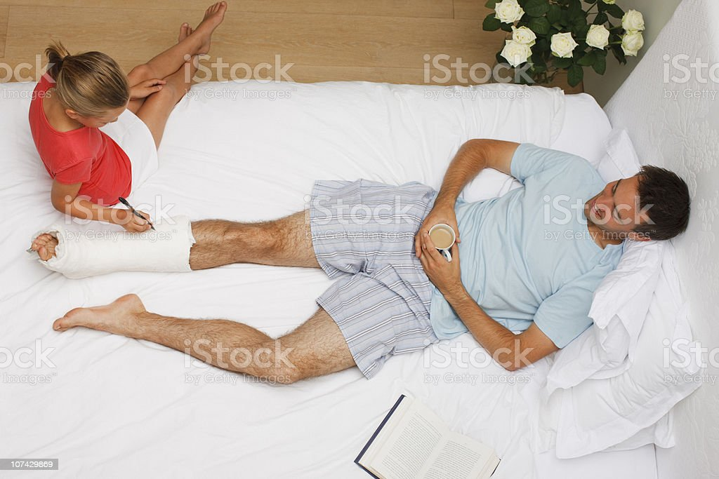Girl signing fathers leg cast stock photo