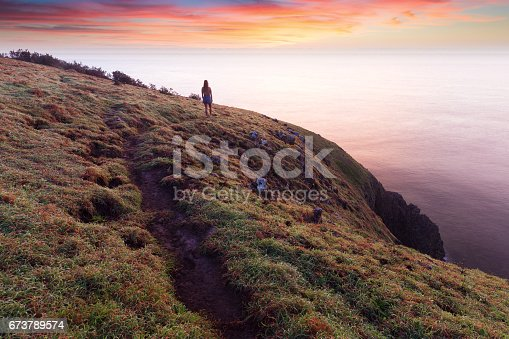 A silhouetted woman walking on a coastal trail, stops to watch a vibrant sunrise near Port Macquarie, Australia.