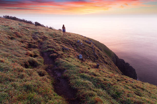 Girl silhouetted at sunrise on a Coastal Trail stock photo