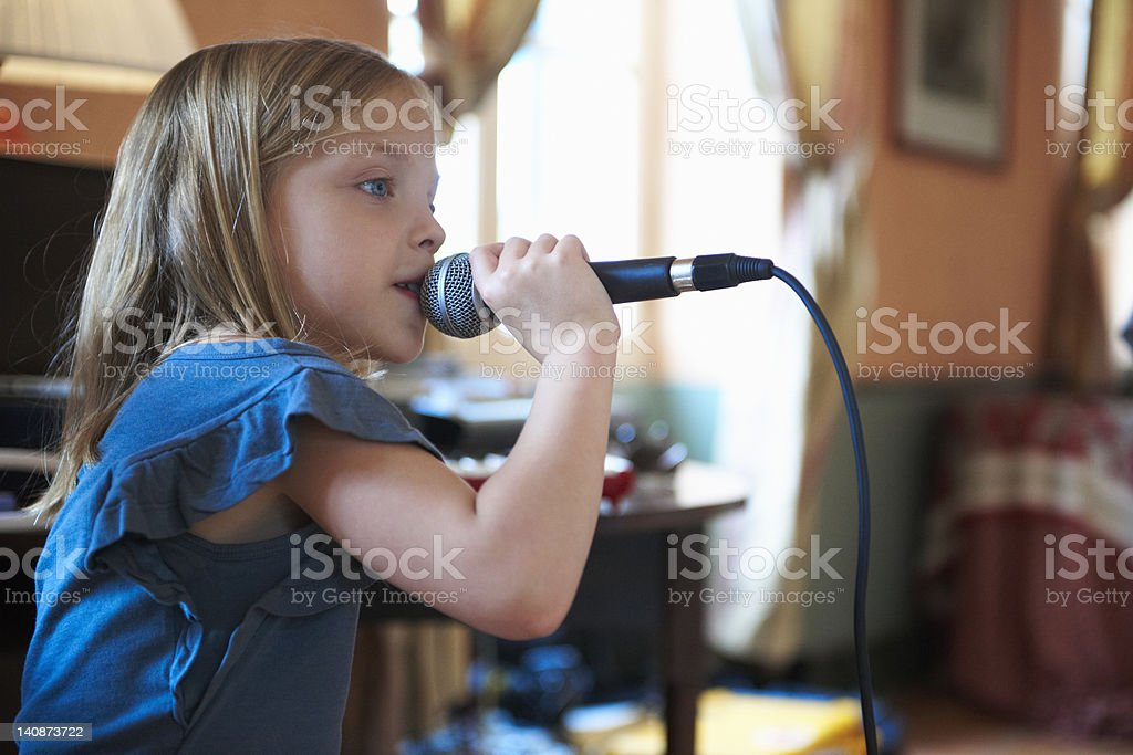 Girl singing into microphone stock photo