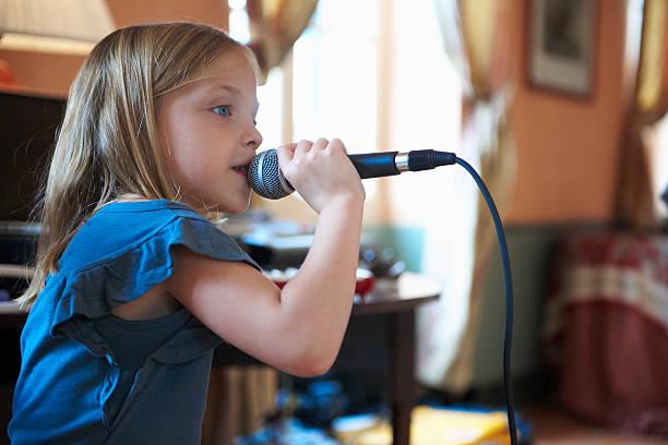 mädchen singen mit mikrofon - one song training stock-fotos und bilder