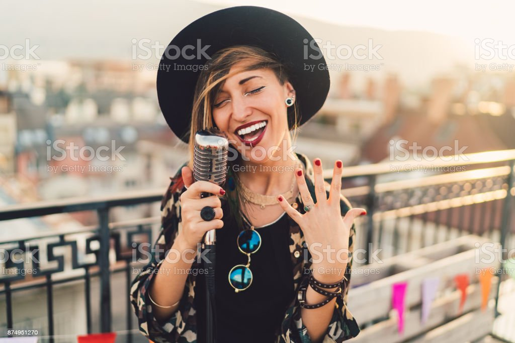 Girl singing on rooftop party stock photo